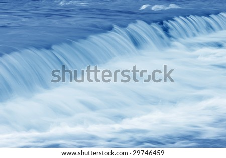 Abstract perspective of a swiftly moving stream with a small waterfall.