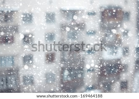 Abstract photo of the snowstorm and residential building on a background - stock photo