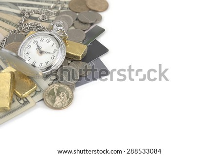 Abstract pocket watch on top of various bank notes, dollar coins, gold bar, and credit cards over white table - stock photo