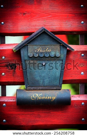 Abstract post box on red wooden gate - stock photo