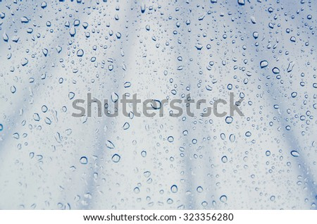 Abstract rain drop on window glass with blur roof background, blue color tone