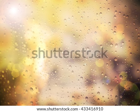 Abstract raindrop on glass window with warm filter  - stock photo