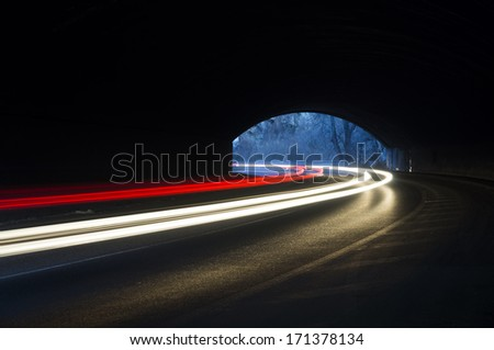 Abstract rays of white and yellow light with a car tunnel as background - stock photo