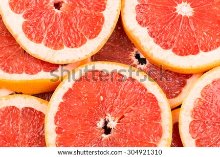 Abstract red background with citrus-fruit of grapefruit slices. Close-up - stock photo