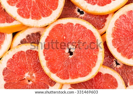 Abstract red background with citrus-fruit of grapefruit slices. Close-up