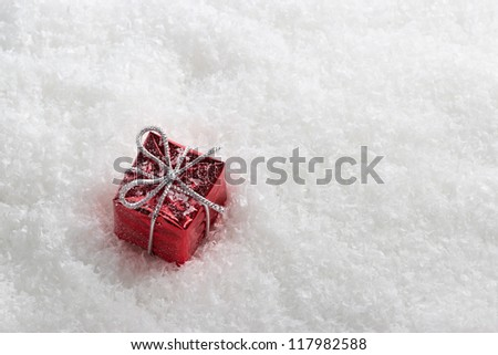 Abstract red gift box with white frost in snow.