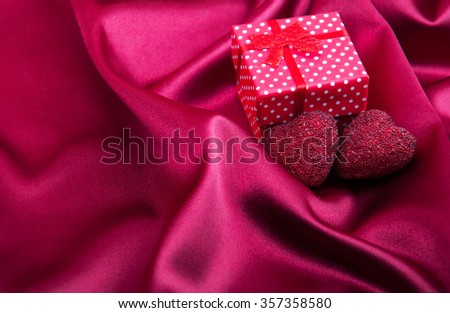 Abstract red silk fabric background  with gift box and hearts - stock photo