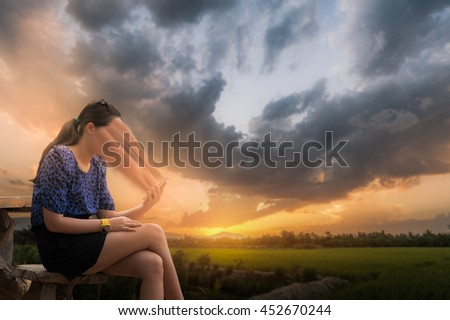Abstract scene of young woman using her phone seriously while sitting outdoor on wood chair in morning time on weekend with blurry nature background. Phone addiction concept.