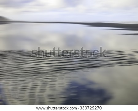 Abstract seascape of sandbar disappearing into large reflective tidal pool along Pacific coast of Olympic Peninsula in the state of Washington, USA, for themes of nature, the environment, or travel