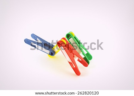 Abstract shape from four color clothes-pegs over white - stock photo