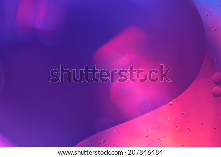 Abstract shapes of pink water forming a wave like a sine-curve in front of a blue blurred background - stock photo