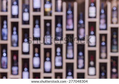 Abstract shelves with bottles of wine, shallow depth of focus - stock photo