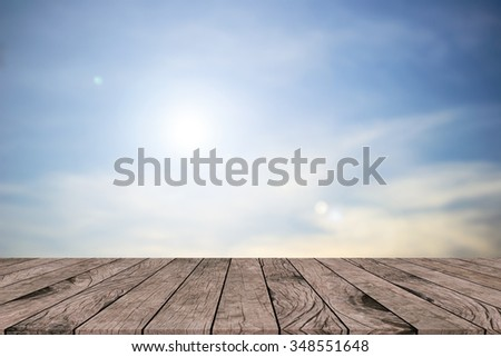 Abstract shining sun rays light on morning sky background with aged retro wood panels table top perspective view.advertising/promote/showing products/goods/items on display montage:patio scene wall. - stock photo