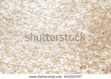 Abstract shiny background with gold sparkles. Texture of beautiful fashion fabrics with light sequins. Pastel color of iridescent fabric