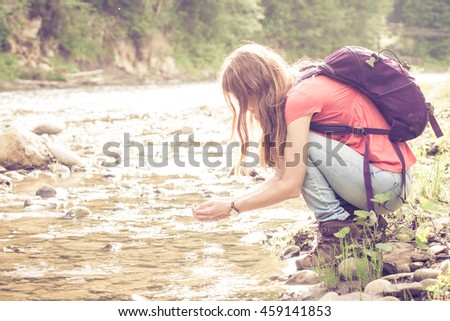 abstract shot of girl hiker drinking a water from the river against a bright sunlight