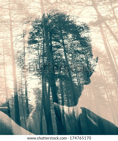 Abstract soft focused duotoned double exposure portrait of woman and black forest  - stock photo