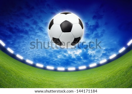Abstract sports background - soccer ball, green stadium, spotlights, dark blue sky - stock photo