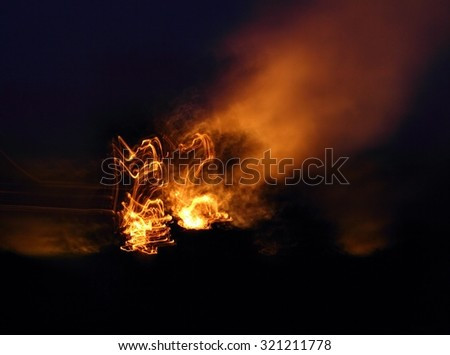 Abstract - stack of hay in fire near the village - stock photo