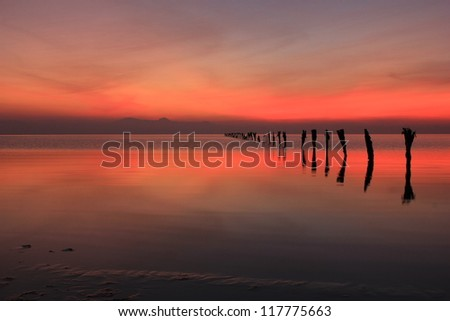 Abstract sunset reflection with old fence posts, Great Salt Lake, Utah, USA.