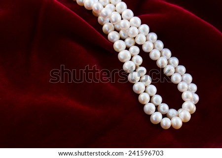 abstract texture of  draped soft red velvet background with pearl jewelery