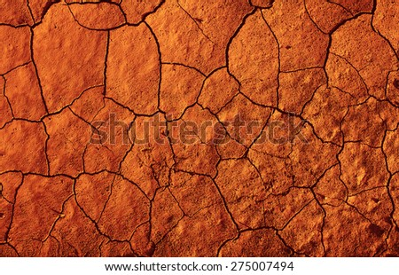 Abstract texture of red-hot cracked dirt as background - stock photo