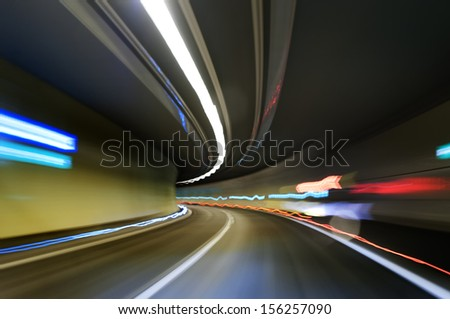 Abstract traffic motion lights in a tunnel - stock photo