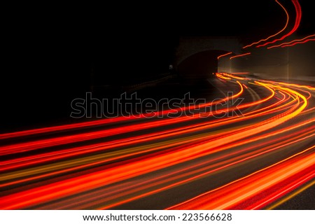 Abstract trails red, yellow and  rays of light in a car tunnel  - stock photo