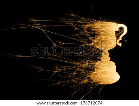 Abstract trophy in bright sparks in landscape orientation with copy space on left on black background. - stock photo