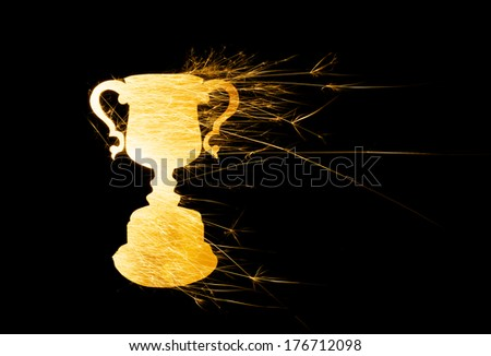 Abstract trophy in bright sparks in landscape orientation with copy space on right on black background. - stock photo