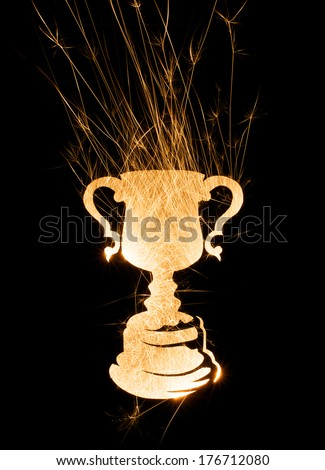 Abstract trophy in bright sparks in portrait orientation with copy space on black background. - stock photo