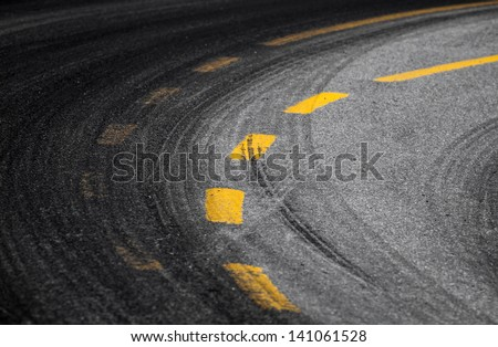 Abstract turning road background with tires track and yellow striped road marking on dark asphalt - stock photo