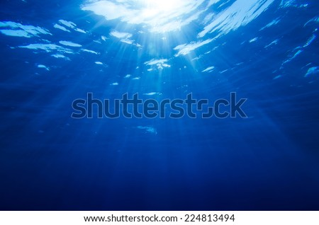 Abstract underwater background with sun rays - stock photo