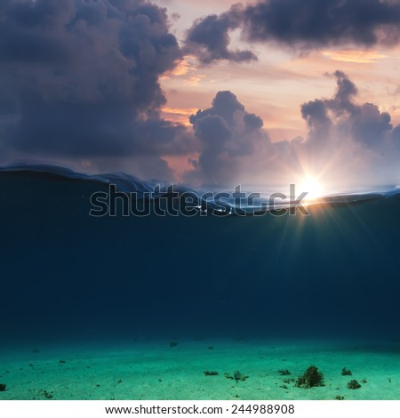 abstract underwater deep with sunset clouds over waterline - stock photo