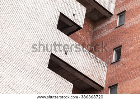 Abstract urban architecture fragment, gray and red brick walls with balcony and windows - stock photo