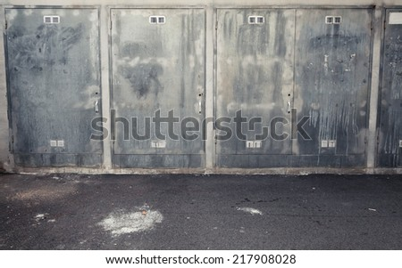 Abstract urban interior background with metal cabinets and asphalt - stock photo