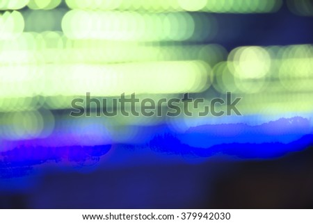 Abstract vibrant blue and green bokeh over dark background - stock photo