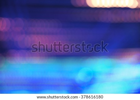 Abstract vibrant blue, violet, and orange bokeh over dark background - stock photo