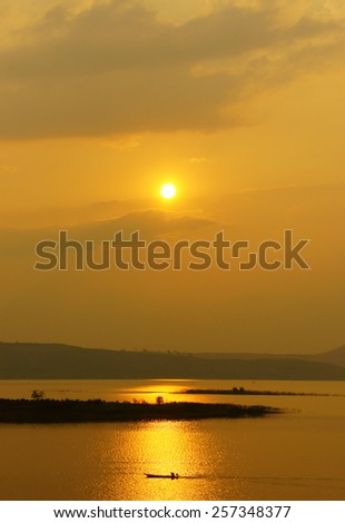 Abstract Vietnamese rural at sunset, sun on yellow sky, vibrant color, silhouette of people rowing a row boat on Nam Ka Lake, Dakak, Vietnam, house on water, make amazing landscape of Viet Nam travel