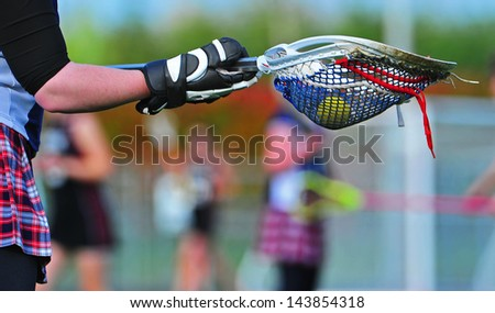 Abstract view from the goal of a girls lacrosse game as the goalie prepares to pass the ball to one of her team mates. - stock photo