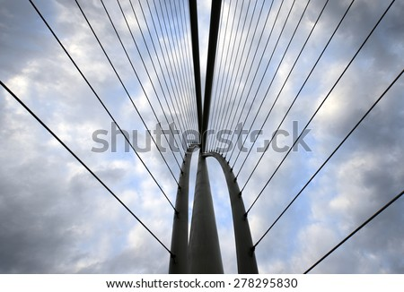 Abstract view of bridge support against a  cloudy sky. - stock photo