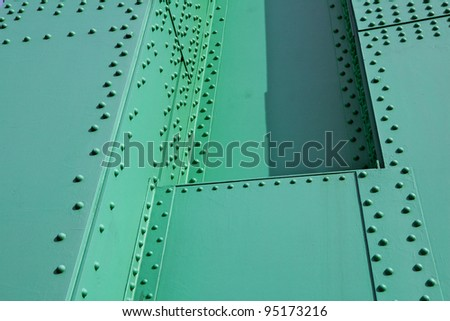 Abstract view of green painted steel beams and girders with many rivets