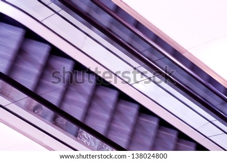 Abstract view of moving purple escalators - stock photo