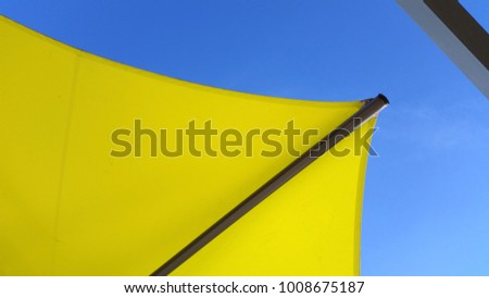 Abstract View of Yellow Sunshade with Blue Sky Background