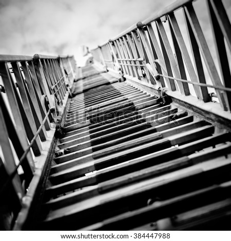 Abstract view through a ladders of fire truck. Black and white processing. - stock photo