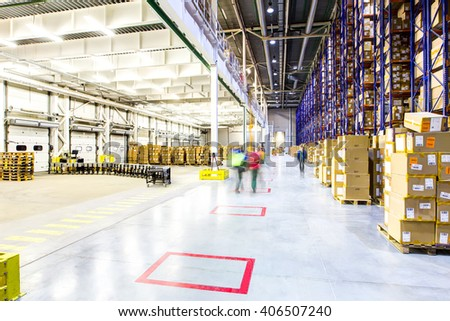 Abstract view, workers quickly walk through the warehouse