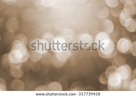 Abstract vintage blurred background of bokeh circle light in sepia ton color tone with shiny light :blur of natural backdrop. - stock photo