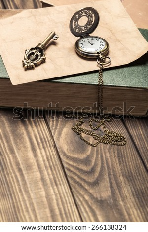 Abstract. Vintage pocket watch, old book and a brass key on a vintage surface - stock photo
