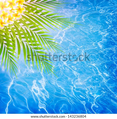 Abstract water background, fresh palm leaves and frangipani flowers on blue sea background, spa resort, summer vacation and holidays, refreshment concept