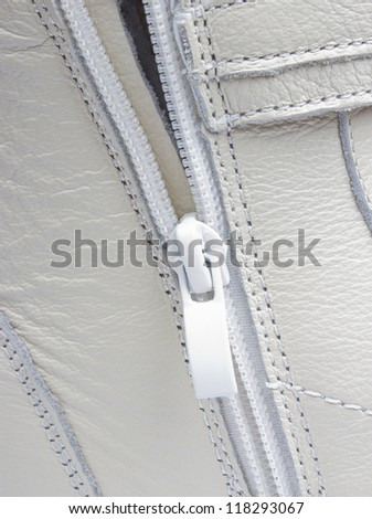 Abstract white leather background with seams and zip, closeup