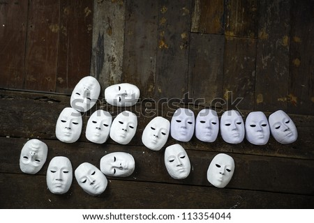 Abstract white masks on wooden background - stock photo